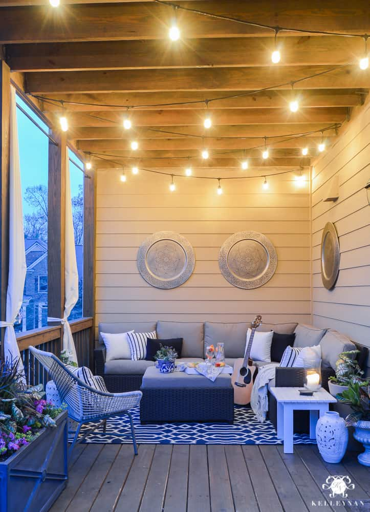 A picture of a covered deck with a comfy sofa at twilight and hanging lights overhead.