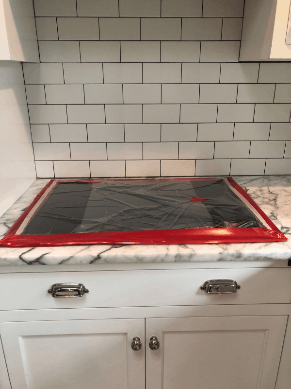 The stovetop that has been taped off before they refinished the marble counters.