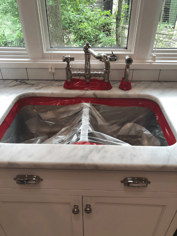 The taped off sink and faucet before they refinished the marble counters.
