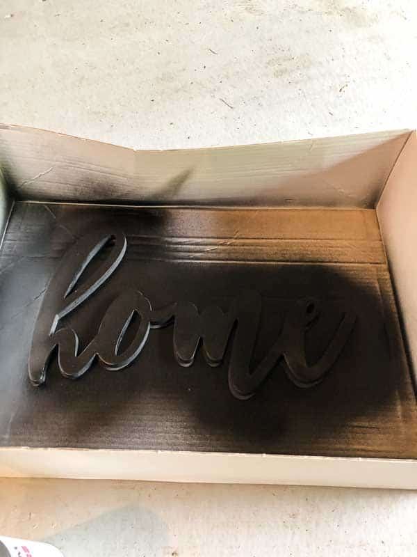 The word home after spray painting it black for my farmhouse sign.