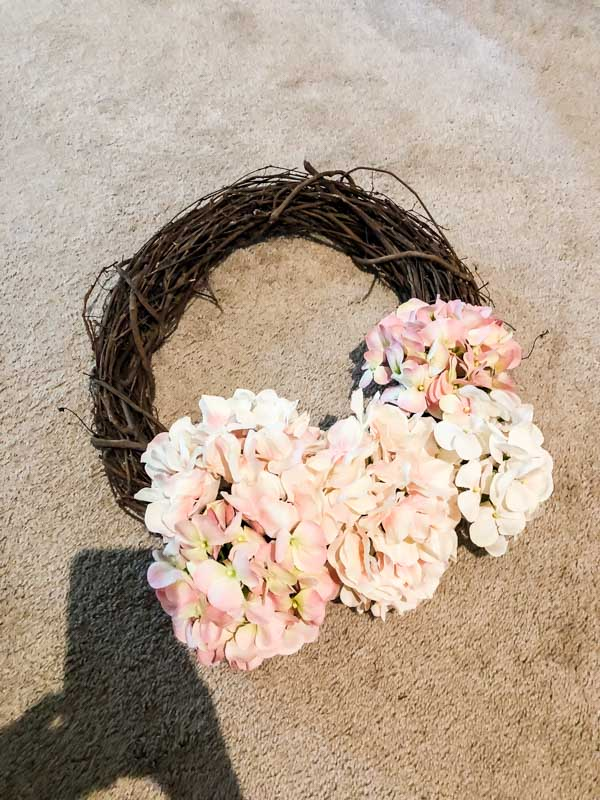 Trying different places to put the hydrangea flowers on the grapevine wreath.