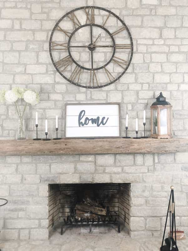 A farmhouse sign on my mantel made using shiplap and the word home.