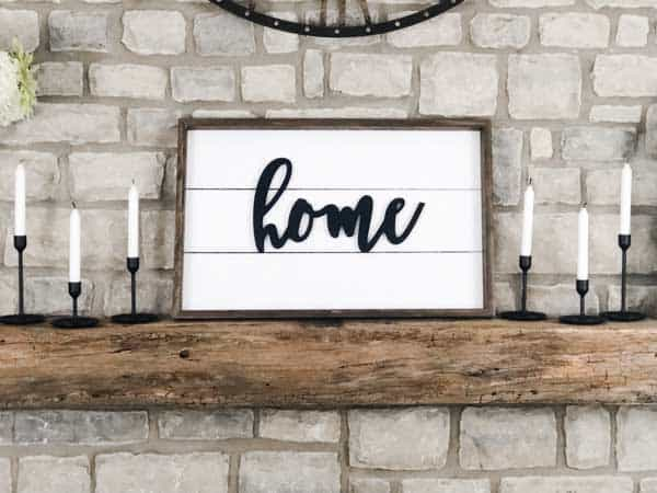 A farmhouse sign on my mantel made using shiplap and the word home on it.