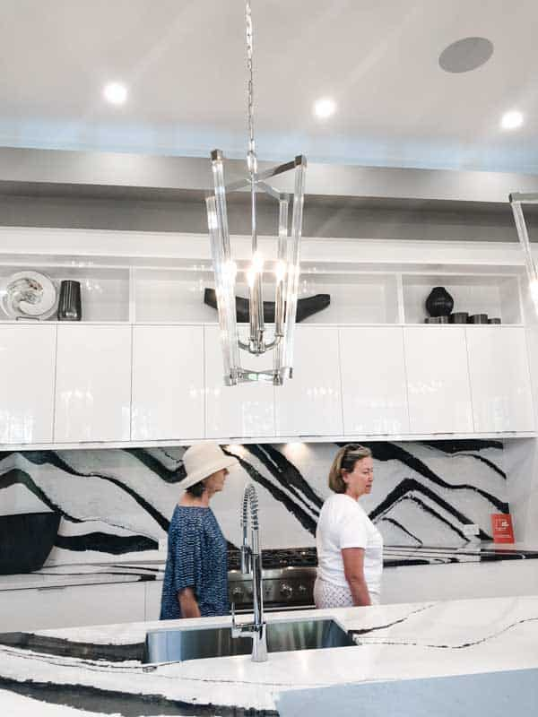Amazing tall pendant lights in silver and glass hanging over a black and white granite island counter.