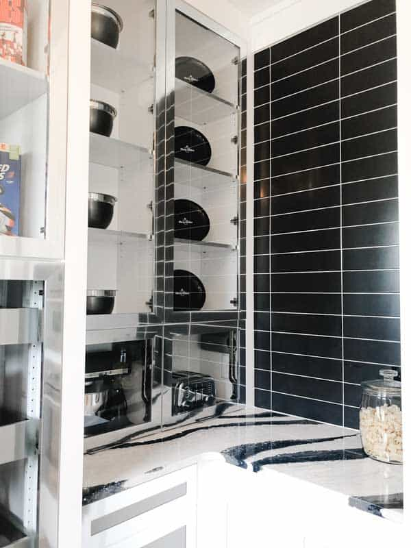 A butlers pantry in a kitchen with black and white counters and black subway tile that is stacked on top of one another rather than brick pattern.