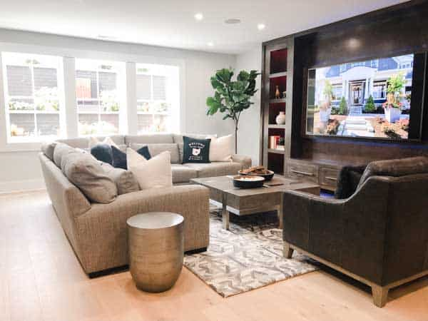 A family room with a huge sectional facing an enormous tv.