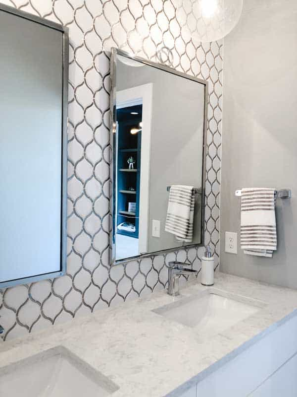 A bathroom with white cabintetry, marble counters and white geometric shaped tile on the wall.