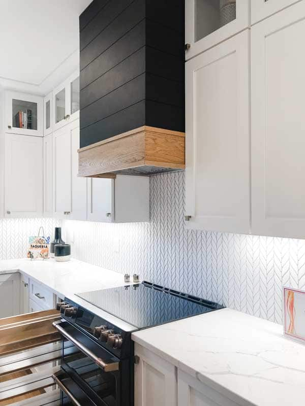 The farmhouse style kitchen with black shiplap on the vent hood.