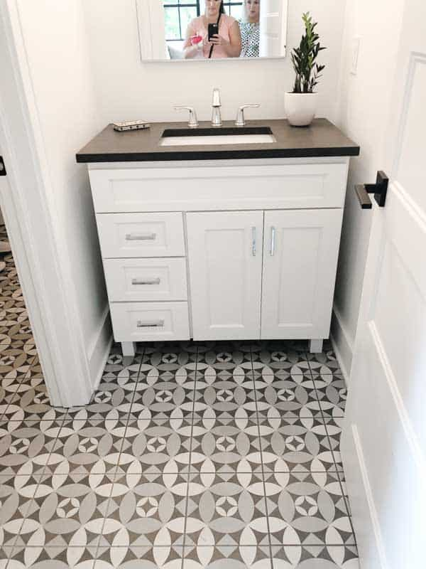 A farmhouse style bathroom with patterned tile floors, white cabinetry and dark counters.