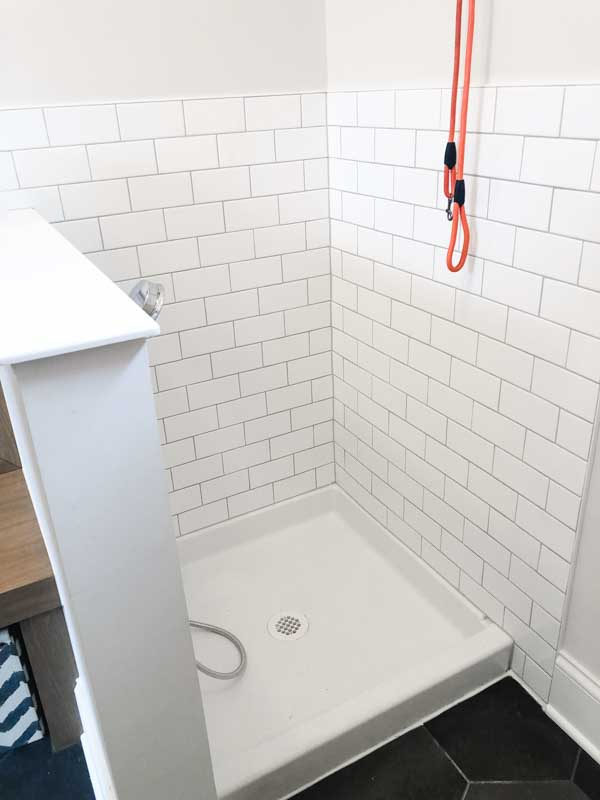 A dog washing station in the laundry room with white subway tile walls.