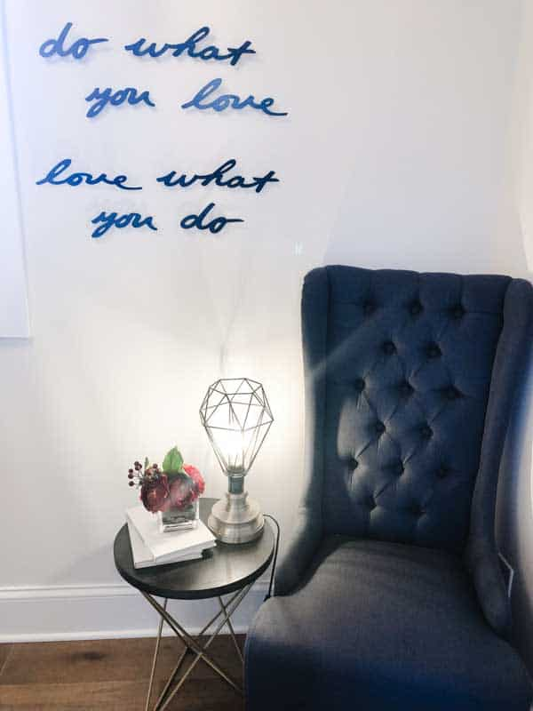 A sitting area with a tall backed chair and wall art that says do what you love, love waht you do.