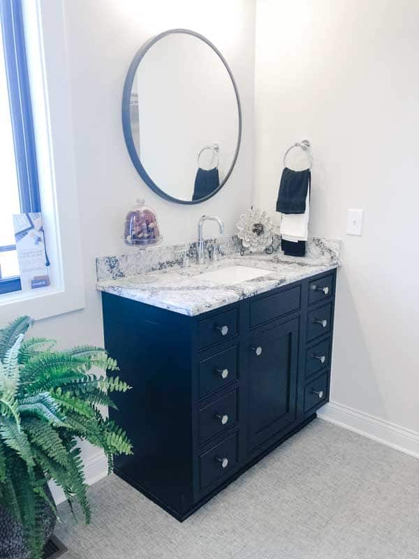 A bathroom vanity with dark cabinets and a round mirror.