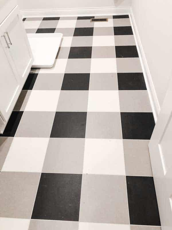 A laundry room floor with a checker board looking patterned tile floor.