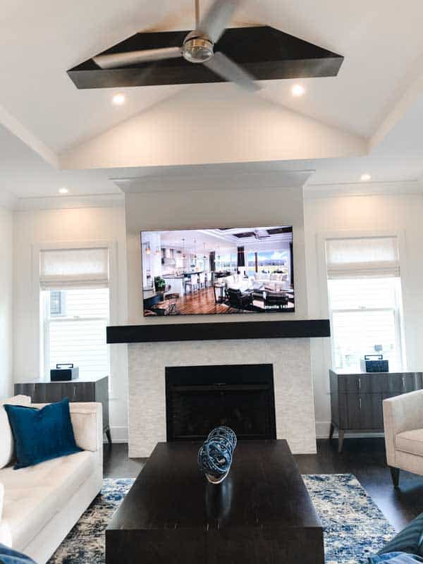 A family room that is done in lots of white with dark wood accents on the coffee table, mantel and ceilinb beam.