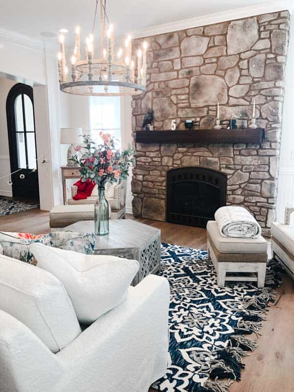 A living room with a two tiered chandelier and a stone fireplace.
