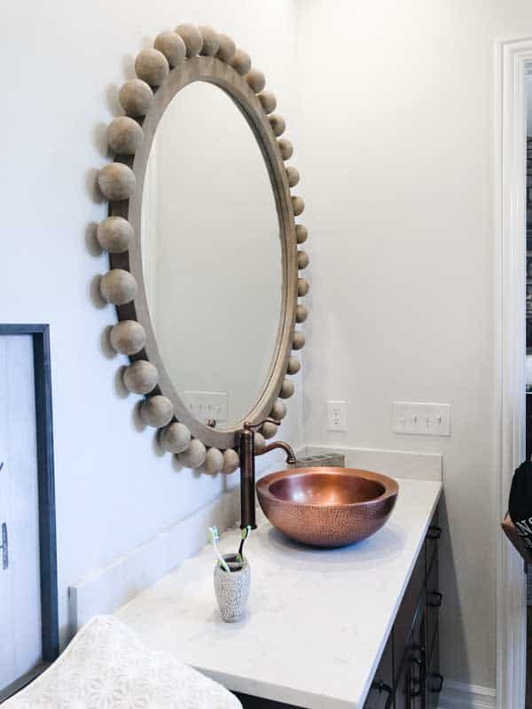 A round mirror in a master bath with balls all around it and a copper sink and faucet.