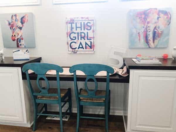Here is a kids desk area with two teal chairs and a sign that says this girl can.