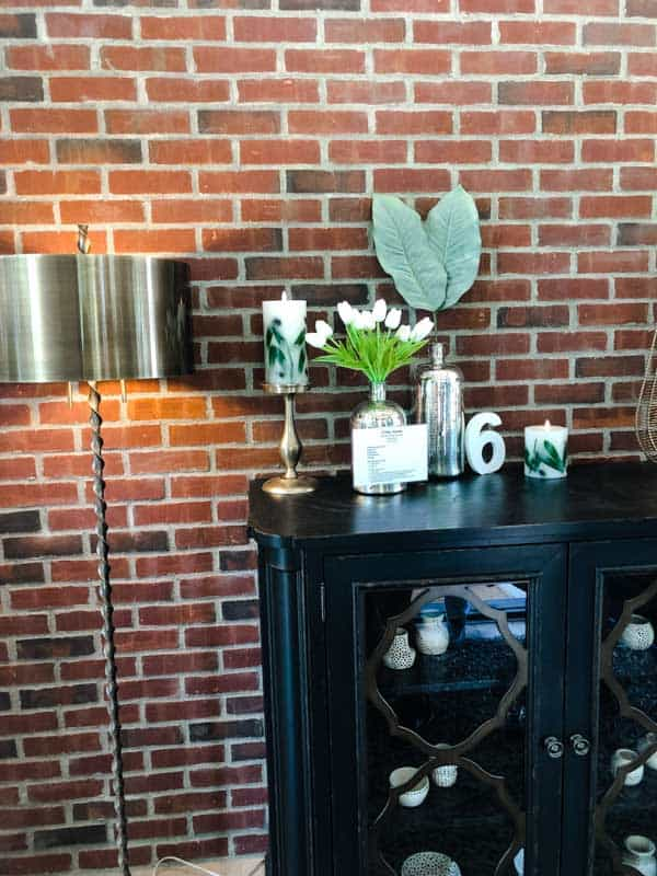 The front entryway of the mascuiline house with a black console table and a brick wall.