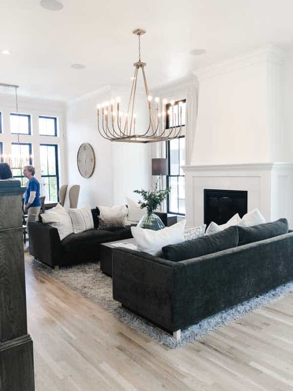 A family room with dark colored couches, white walls, tons of windowns and a massive square chandelier made of gold.