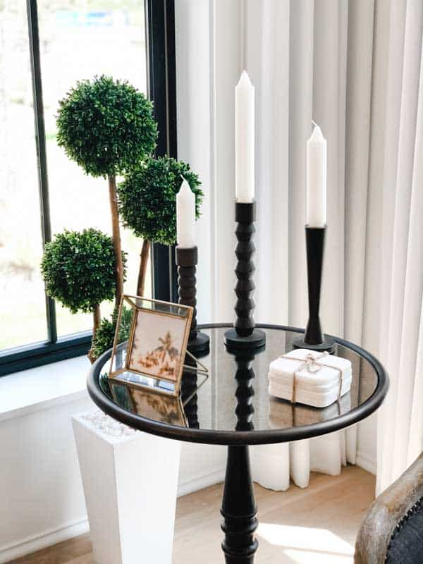 A vignette of candle sticks, a pretty gold fram and white coasters on a black metal table with an antiqued glass top.