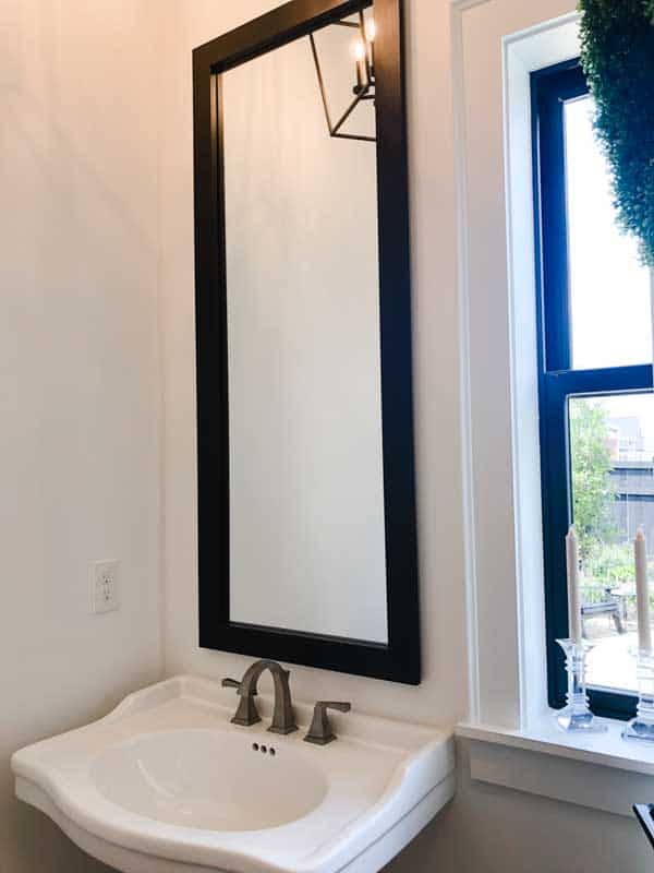 Powder bathroom with a pedestal sink and a very tall mirror with a black frame.