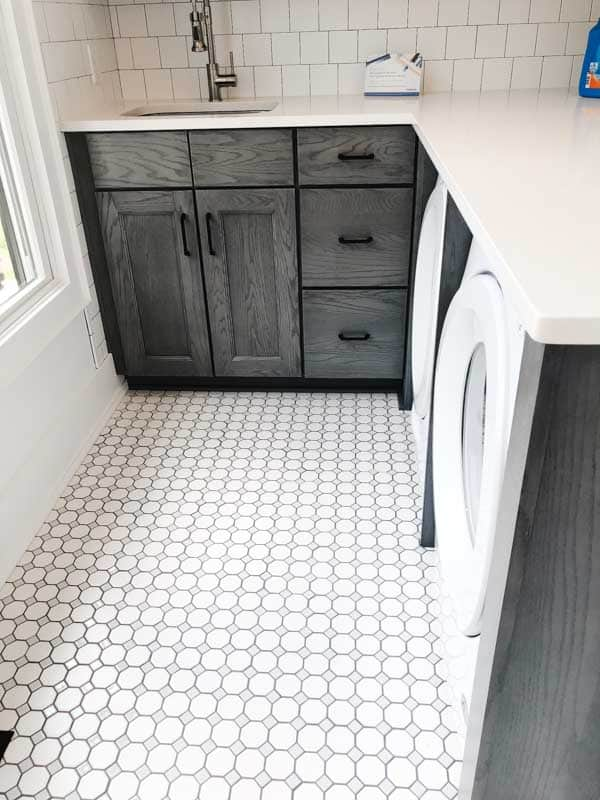 A laundry room with dark cabinets and a pretty patterned tiled floor reminicent of the 1960's.