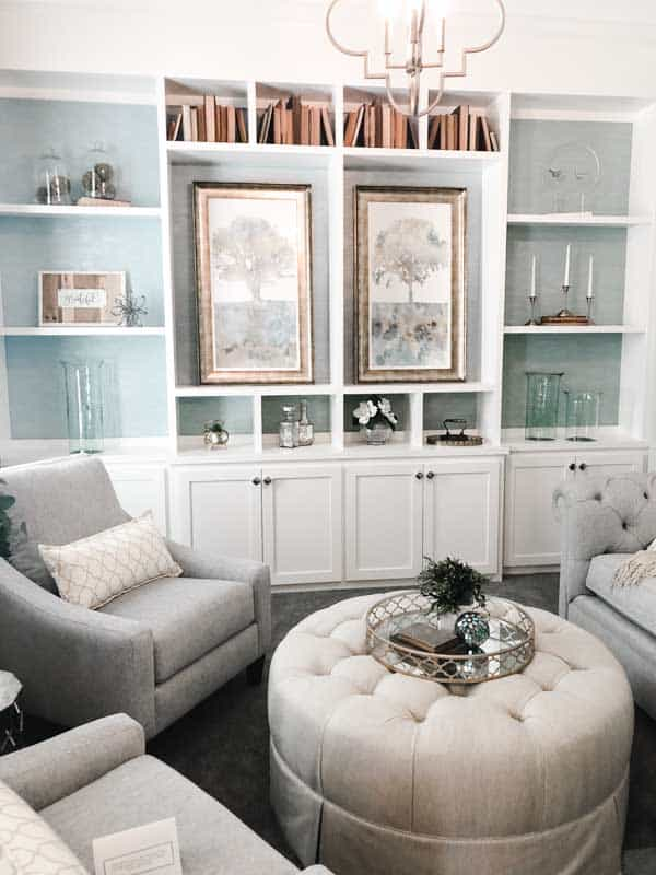 an entertaining space with four club chairs and an ottoman. There are white builtins with a turqoise grass cloth wallpaper.