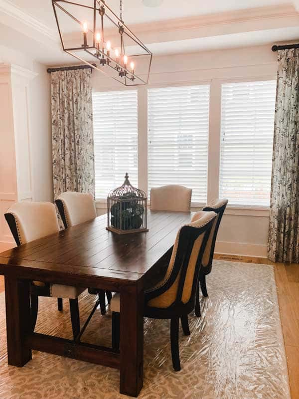 A smaller dining room with a very long 6 light lightfixture and long hanging drapes flanking the windows.