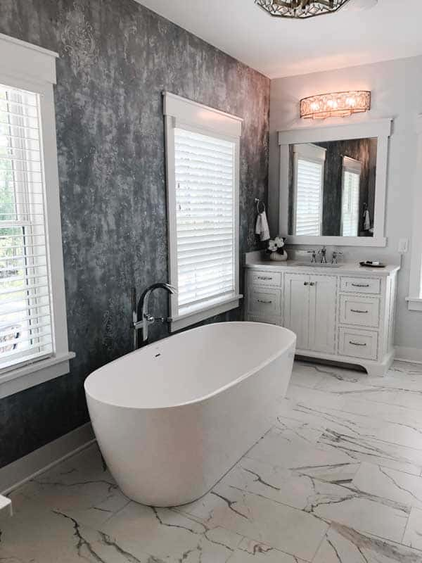 A black and whtie bathroom with a large egg shaped free standing tub on marble floor tiles.