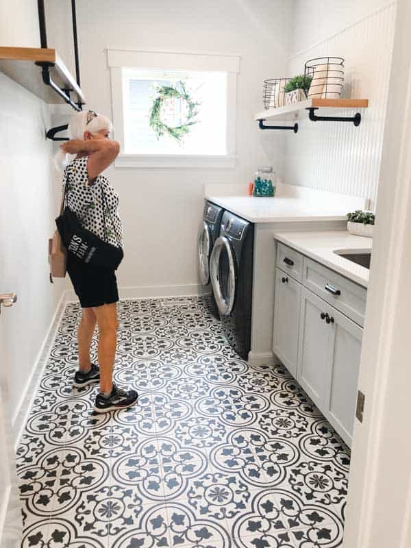 A farmhouse style laundry room with black and white patterend floor tile.