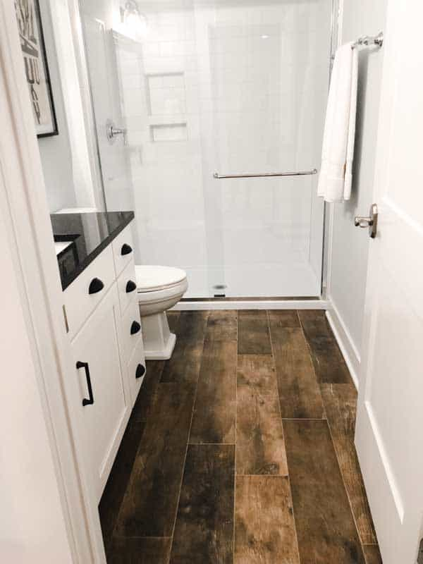A white bathroom with balck counters and a floor tile that looks like reclaimed wood.