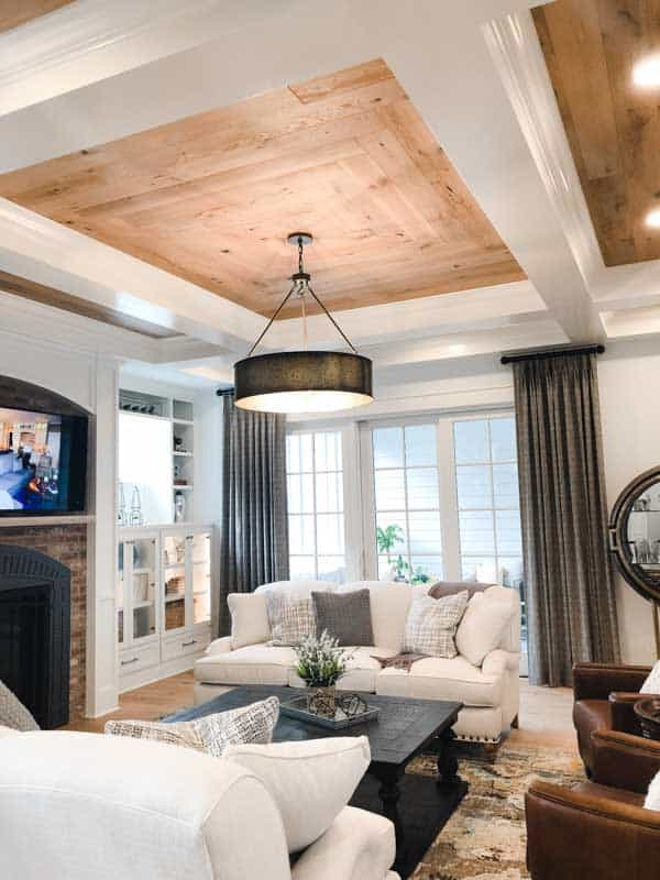 A view of family room furniture, transitional sofas, leacher chairs and a wooden coffee table on a light colored rug.
