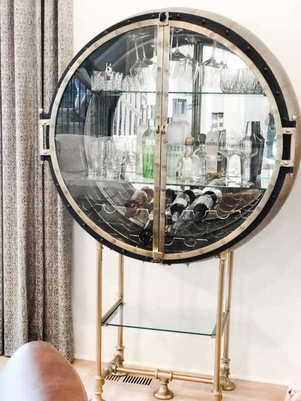A bar cart that looks like a porthole on a ship.