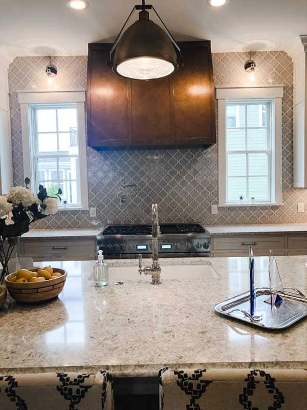 A very large copper hood over a 6 burner stove with a beautiful arabesque tile in light gray.