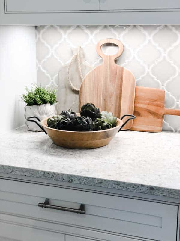A pretty vignette of cutting boards, a pland and a bowl of artificial artichokes on a kitchen counter with a gorgeous arabesque backsplash in light gray.