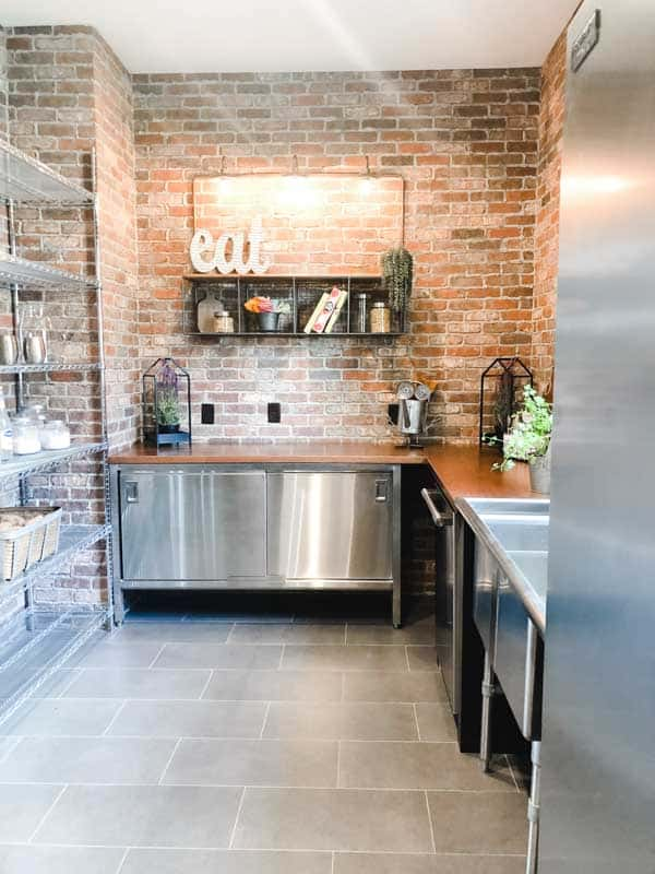 A butlers pantry that looks more like an industrial kitchen with metal shelves and stainless steel workspaces.