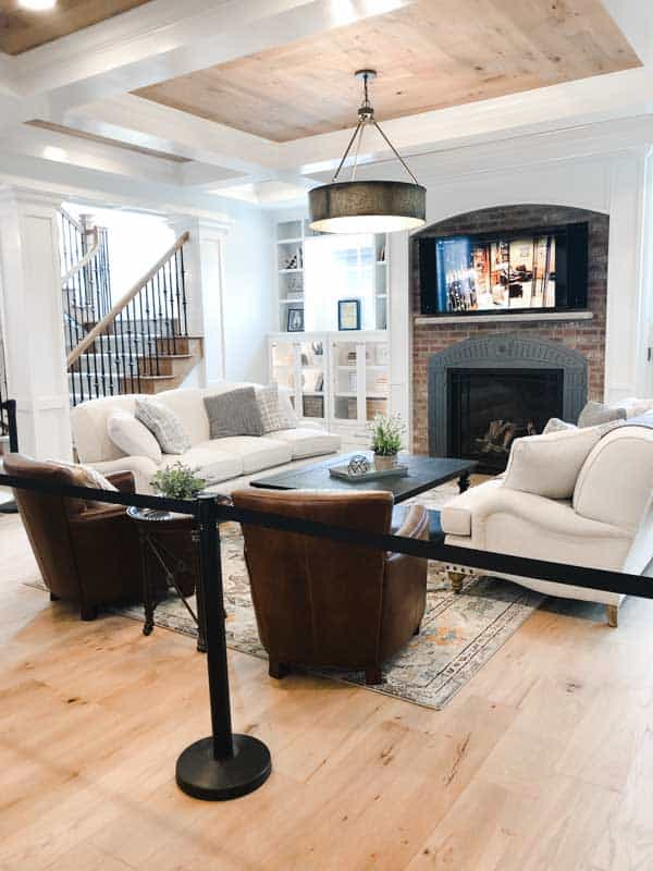 A beautiful family room with a reclaimed red brick fireplace and builtins on either side and a coffered ceiling with reclaimed wood in the middle.