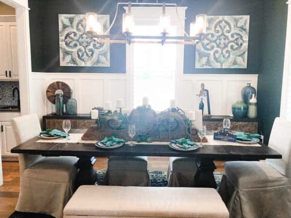 A very pretty dining room with board and batten painted white with teal walls and accessories.