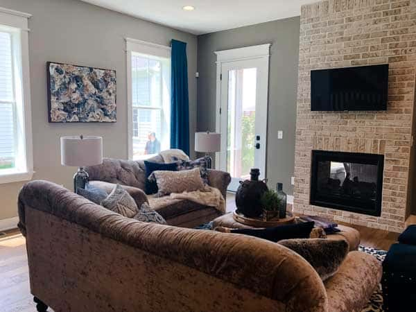 A family room with a light colored brick fireplace and TV mounted above.