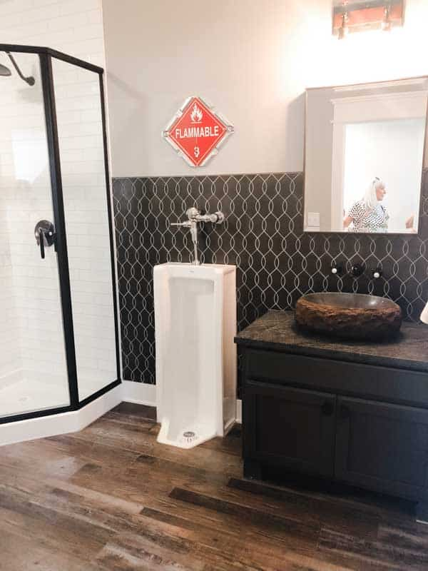 A fireman themed basement bathroom with a urinal!
