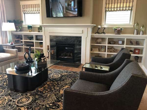 A family room with furniture centered around a fireplace with builtins on either side and a TV mounted above.