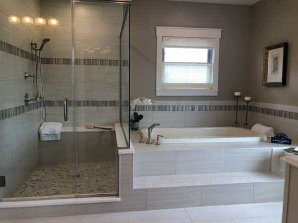 A master bathroom that has a step up to a large tup and a generously sized shower right next to it.