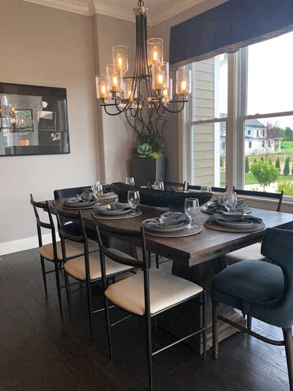 This dining table is made of dark wood with metal side chairs and dark blue upholstered head chairs. The lighting is a chandelier that is two tiered.
