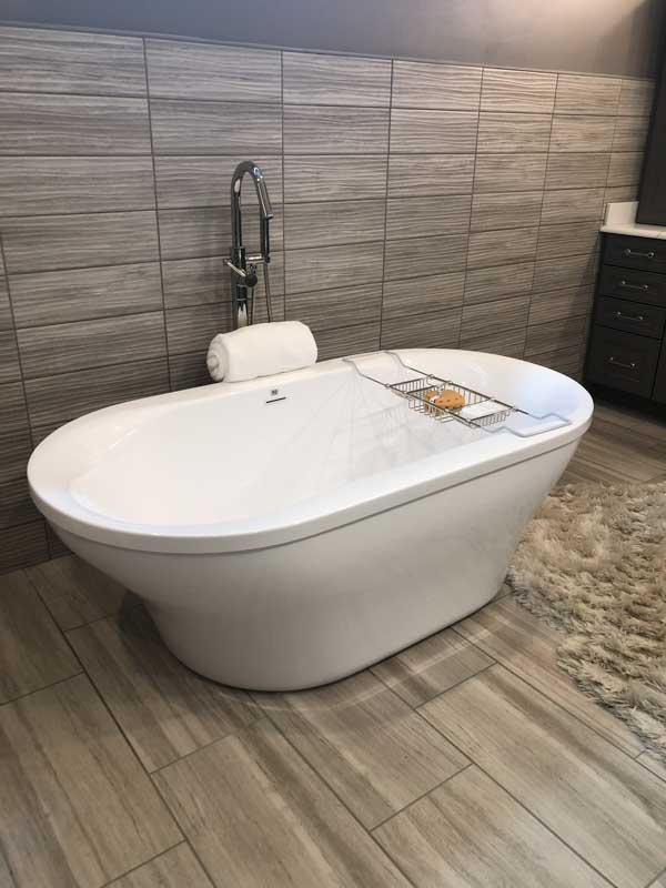 An amazing modern bathtub with porcelin tile on the wall and floor.