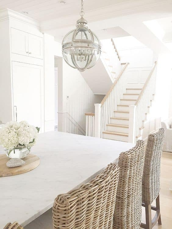 A kitchen and stair well with white walls and white trim.