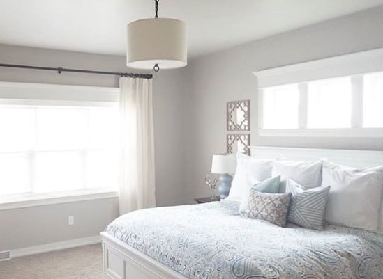 A bedroom painted in Sherwin Williams Agreeable Gray.