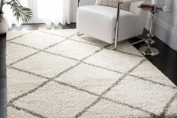 A white shag rug with a gray diamond pattern.