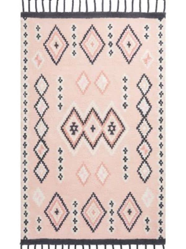 A rug with tassles, a pink background and a black diamond pattern on it.