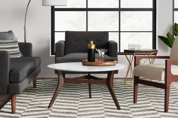 A herringbone style rug with midcentury modern furniture on it in dark wood and whites.