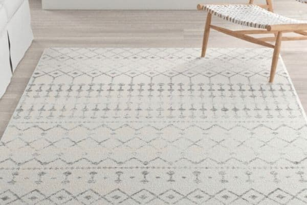 A white rug with gray geometric shapes on a light wood floor.